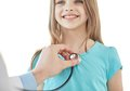 Close up of happy girl and doctor on medical exam Royalty Free Stock Photo