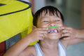 Close up of happy little boy make big eye with metal crowns Royalty Free Stock Photo