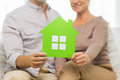Close up of happy senior couple with green house family relations real estate age and people concept paper cutout at home Royalty Free Stock Photography