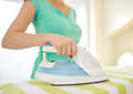 Close up of happy woman with iron ironing at home Royalty Free Stock Photo