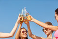 Close up of happy young women clinking bottles summer vacation holidays party travel and people concept with drinks Royalty Free Stock Image
