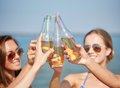 Close up of happy young women with drinks on beach summer vacation holidays party travel and people concept clinking bottles Royalty Free Stock Photos