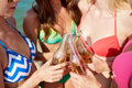 Close up of happy young women with drinks on beach summer vacation holidays party travel and people concept clinking bottles Stock Images