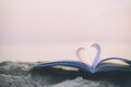 Close up heart book on sand in the beach with vintage filter blur background Royalty Free Stock Photo