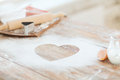 Close up of heart of flour on wooden table at home Royalty Free Stock Photography