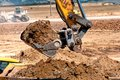 Close up of heavy duty excavator scooping into earth and loading a dumper truck Stock Photos
