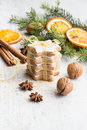 Close up of homemade butter nuts star shaped cookies with icing, pine, orange slices,cinnamon, anise, walnuts and golden ribbon ov Royalty Free Stock Photo