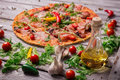 A close-up of hot margarita pizza on a rustic table background. Whole Italian pizza with vegetables and olive oil. Royalty Free Stock Photo