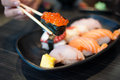Close up of Ikura suhi in chopsticks and Variety Sushi Set Royalty Free Stock Photo