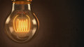 Close up of an illuminated vintage hanging light bulb over dark background Royalty Free Stock Photo