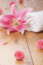 Close up image of beautiful pink flowers and a white towel on a wet wooden background Stock Photo