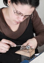 Close up image of a female jeweler filing a piece of metal in her workshop Stock Photography