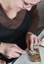 Close up image of a female jeweler filing a piece of metal in her workshop Stock Images