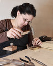 Close up image of a female jeweler hammering a piece of metal in her workshop there is an intended motion blur on the hammer Stock Image