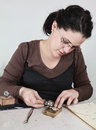 Close up image of a female jeweler working on a piece of metal in her workshop Royalty Free Stock Photography
