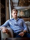 Nice bearded male in blue shirt sitting on the edge of the sofa Royalty Free Stock Photo