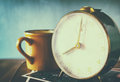 Close up image of old clock and cofee cup over wooden table. image is filtered with retro faded style Royalty Free Stock Photo