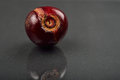Close up of image of rotten red cherry fruit on reflective black Royalty Free Stock Photo