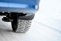 Close-up Image of Winter Car Tire on Snowy Road. Drive Safe Concept. Royalty Free Stock Photo