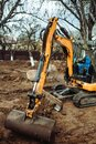 Close up of industrial mini excavator scoop moving earth and doing landscaping works Royalty Free Stock Photo