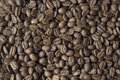 CLOSE UP OF JAMAICA BLUE MOUNTAIN COFFEE BEANS DARK BACKGROUND AND TEXTURE TOP VIEW Royalty Free Stock Photo