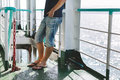 Close up of legs of young man traveller standing on the boat Royalty Free Stock Photo