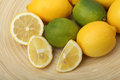 Close-up of lemons and limes on a wooden plate on green background Stock Photo