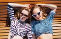 Close up lifestyle summer portrait of two girls friends relaxed and getting sunbathe, laying on the beach, wearing bright marine Royalty Free Stock Photo