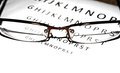 Close-up look of glasses with a letters in the back Royalty Free Stock Photo