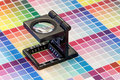 Close-up of a loupe on a colorful test print Royalty Free Stock Photo