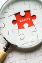 Close up Magnifying glass searching missing puzzle peace identity Royalty Free Stock Photo