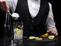 Close-up of making a refreshing shake process. Bartender adding crushed ice to a citrus cocktail on a black background. Royalty Free Stock Photo