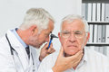 Close up of a male doctor examining senior patient s ear at the medical office Stock Image