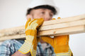 Close up of male in gloves carrying wooden boards repair building and home concept and helmet on shoulder Stock Photos