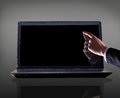 Close up of male hand with forefinger pointing at laptop screen over black background Stock Photos