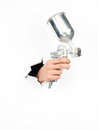 Close up male hand holding silver spray gun torn white paper isolated Royalty Free Stock Photo