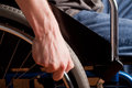 Close up of male hand on wheel of wheelchair selective focus Royalty Free Stock Images