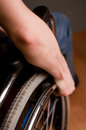 Close up of male hand on wheel of wheelchair selective focus Stock Photos