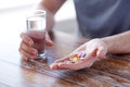 Close up of male hands holding pills and water Royalty Free Stock Photo