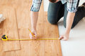 Close up of male hands measuring wood flooring repair building and home concept Stock Photos