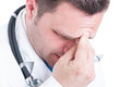 Close-up of male medic pressing his forehead like feeling pain Royalty Free Stock Photo