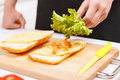 Close up of man adding lettuce leaves to sandwich Royalty Free Stock Photo