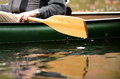 Close up of a man in a canoe image on river green with wooden paddle Stock Images