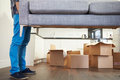 Close up of man carrying sofa as he moves into new home with cardboard boxes in background Royalty Free Stock Photography