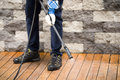 Close up of a man cleaning terrace with a power washer - high water pressure cleaner on wooden terrace surface Royalty Free Stock Photo