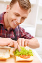 Close up of man decorating bread with lettuce diligent work smiling handsome Royalty Free Stock Photos