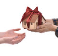 Close-up of man giving wooden house model tied with a bow to wom Royalty Free Stock Photo