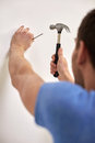 Close up of man with hammer hammering nail in wall reapir building people and home renovation concept Royalty Free Stock Image