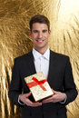 Close up of man hands holding gift box over gold background Stock Photo