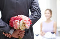 Close up of man hiding flowers behind from woman restaurant people celebration and holiday concept men women at restaurant Stock Photography